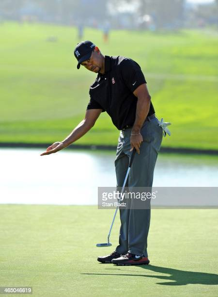Tiger Woods reacts to his putt on the 18th hole during the third round of the Farmers Insurance Open at Torrey Pines Golf Course on January 25, 2014...