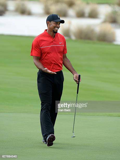 Tiger Woods reacts with a surprise after making a birdie putt on the eighth hole during the final round of the Hero World Challenge at Albany course...