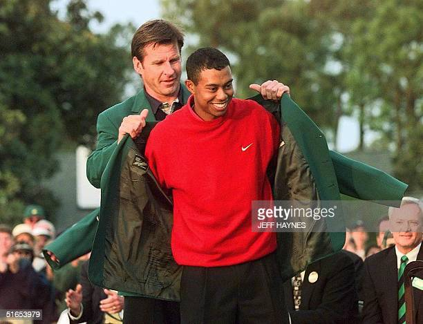Tiger Woods receives the Masters green jacket for winning the 1997 Masters Tournament 13 April from 1996 winner Nick Faldo at Augusta National Golf...