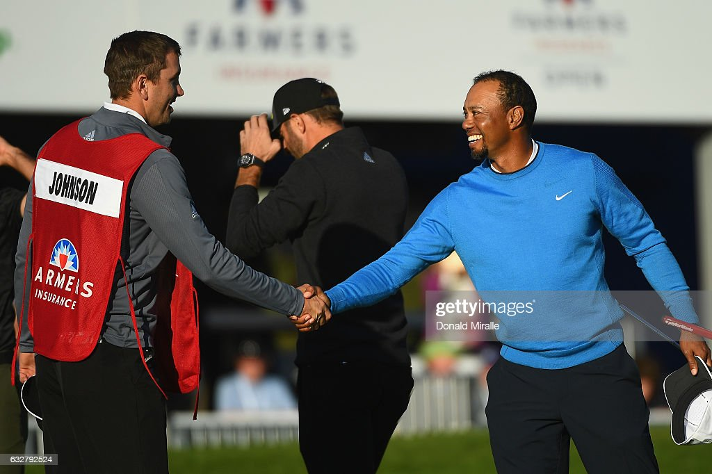 Tiger Woods shakes hands with Dustin Johnson caddie Austin Johnson during the first round of the Farmers Insurance Open at Torrey Pines South on January 26, 2017 in San Diego, California.