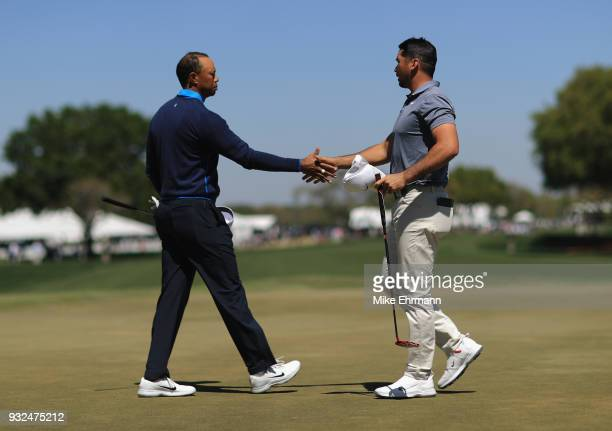 Tiger Woods shakes hands with Jason Day of Australia after their round on the ninth hole during the first round at the Arnold Palmer Invitational...