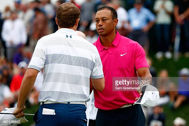 Tiger Woods shakes hands with Jordan Spieth on the 18th green during the first round of the Waste Management Phoenix Open at TPC Scottsdale on...