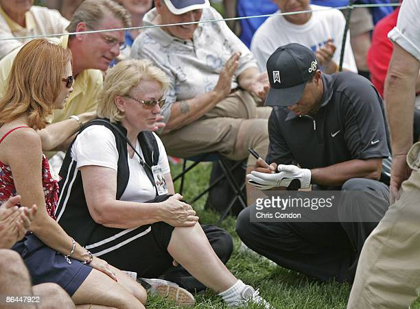 Tiger Woods signs a glove for a spectator who he hit with a ball in the third round of the Memorial Tournament at Muirfield Village Golf Club Dublin...