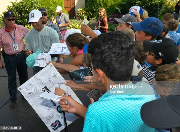Tiger Woods signs autographs for fans after the first round of the BMW Championship at Aronimink Golf Club on September 6 2018 in Newtown Square...