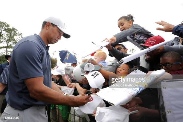 Tiger Woods signs autographs for young fans during a practice round for The PLAYERS Championship on The Stadium Course at TPC Sawgrass on March 12,...