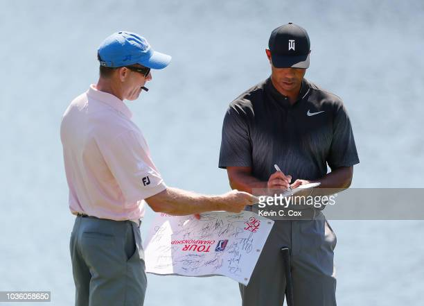 Tiger Woods signs autographs on the chipping green during practice for the Tour Championship at East Lake Golf Club on September 19 2018 in Atlanta...