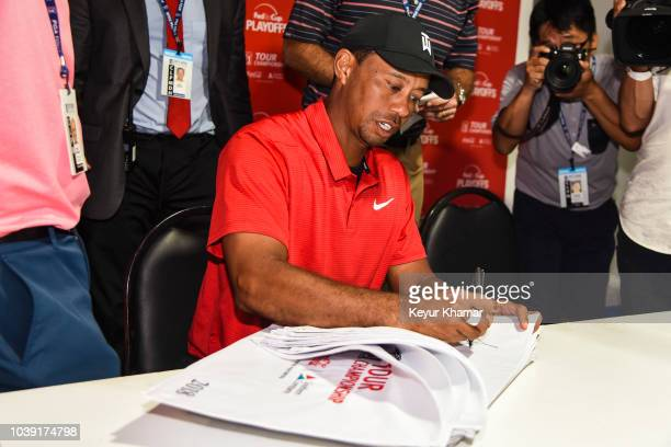 Tiger Woods signs pin flags during a press conference following his two stroke victory during the final round of the TOUR Championship the final...