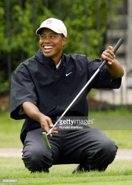 Tiger Woods smiles after John Cook made a long putt on the 18th hole during the second round of the EDS Byron Nelson Championship on May 14, 2004 on...
