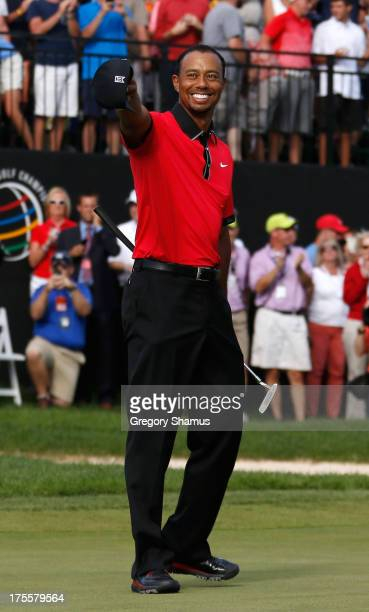Tiger Woods smiles and points to the crowd on the 18th green after the Final Round of the World Golf Championships-Bridgestone Invitational at...