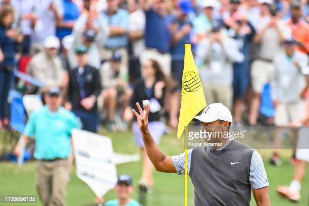 Tiger Woods smiles and waves his ball to fans after holing out for eagle from the 13th hole fairway during the third round of the World Golf...