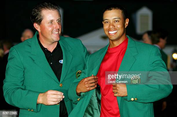 Tiger Woods smiles as he is presented with the green jacket by Phil Mickelson after Woods won The Masters at the Augusta National Golf Club on April...