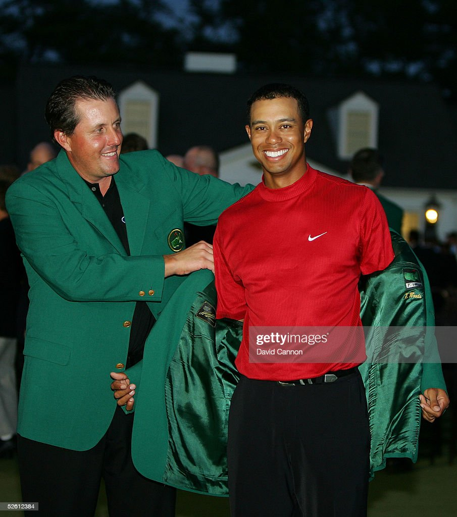 Tiger Woods smiles as he is presented with the green jacket by Phil Mickelson after Woods won The Masters at the Augusta National Golf Club on April 10, 2005 in Augusta, Georgia.