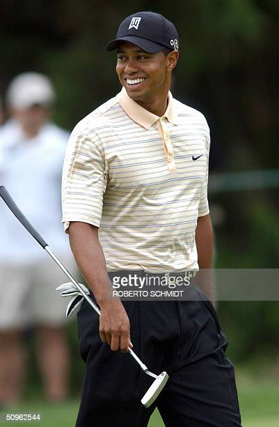 Tiger Woods smiles as he practices putting on the 11th hole during the 2nd day of practice rounds in preparation for the 2004 U.S. Open Championship...