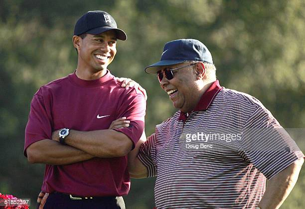 Tiger Woods smiles as he stands with his father, Earl Woods, during the trophy presentation of the Target World Challenge on December 12, 2004 at...