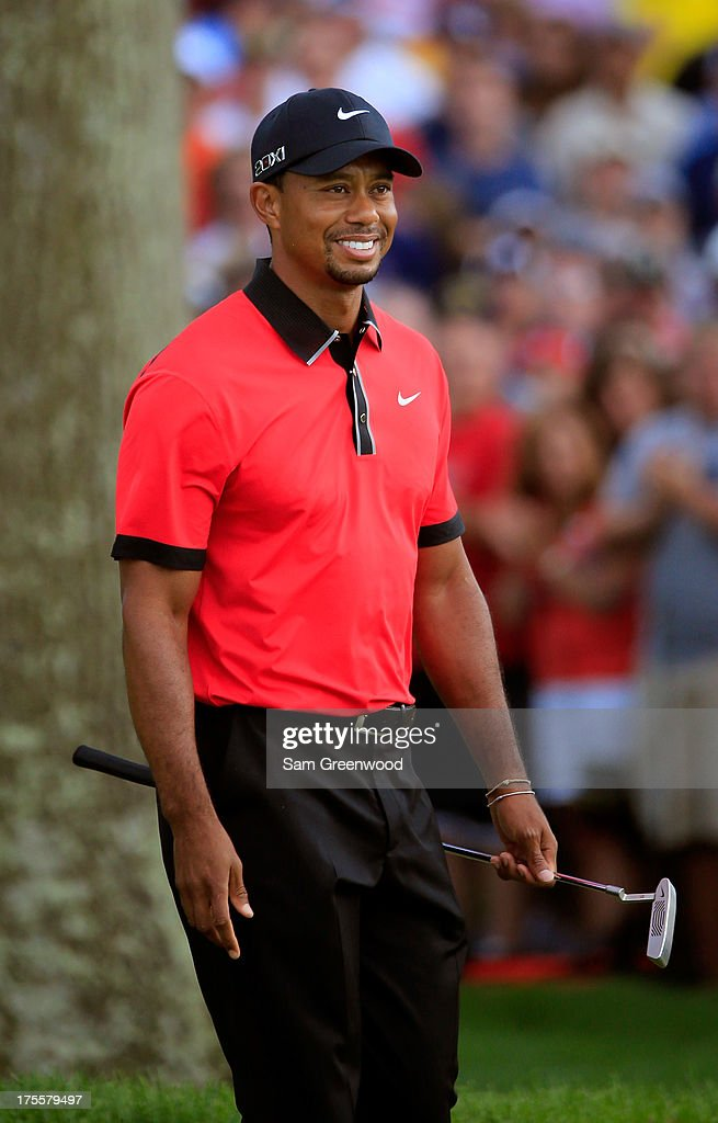 Tiger Woods smiles while walking up to the 18th green during the Final Round of the World Golf Championships-Bridgestone Invitational at Firestone Country Club South Course on August 4, 2013 in Akron, Ohio.