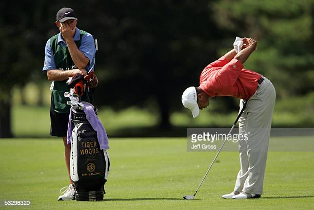 Tiger Woods stretches on the seventh hole as caddie Steve Williams looks on during the first round of the Buick Open July 28 2005 at the Warwick...