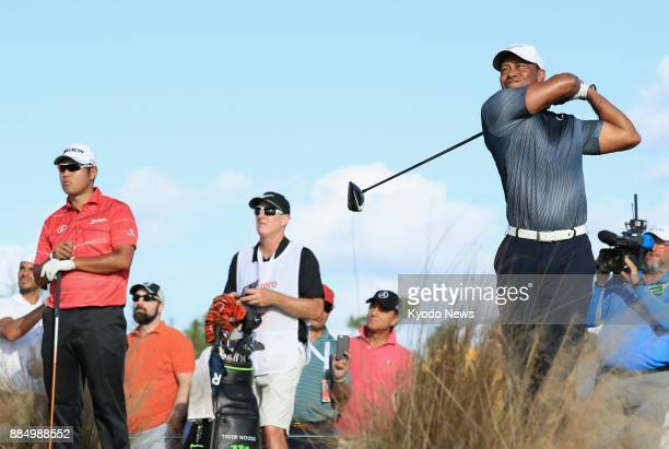 Tiger Woods tees off on the 13th hole as Hideki Matsuyama looks on during the third round of the Hero World Challenge at Albany Golf Club in the...