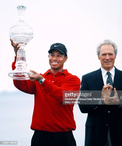 Tiger Woods triumphantly lifts the Waterford crystal trophy he won in the ATT Pebble Beach National ProAm on Monday afternoon Tournament chairman and...
