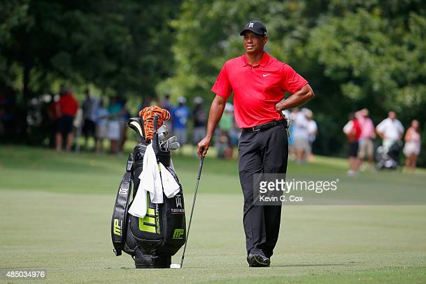 Tiger Woods waits to play his second shot on the fourth hole during the final round of the Wyndham Championship at Sedgefield Country Club on August...
