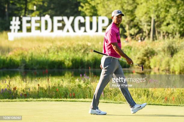Tiger Woods walks past the FedExCup Playoffs sign on the 16th hole green during the second round of the Dell Technologies Championship at TPC Boston...