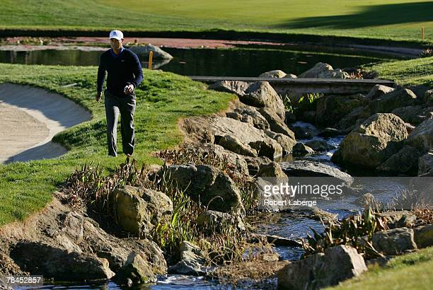 Tiger Woods walks to the 18th green as he prepares to drop the ball after sending his approach shot in a creek next to the green during round one of...