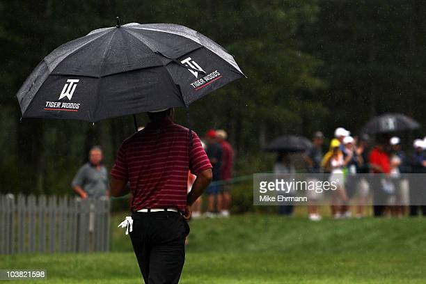 Tiger Woods walks with an umbrella as it rains during the first round of the Deutsche Bank Championship at TPC Boston on September 3, 2010 in Norton,...