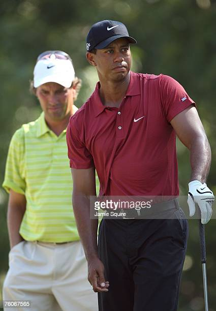 Tiger Woods watches a tee shot as Stephen Ames of Canada looks on during the final round of the 89th PGA Championship at the Southern Hills Country...
