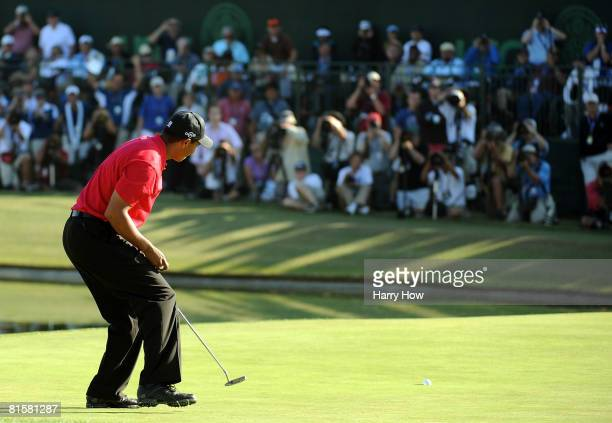 Tiger Woods watches as his birdie putt on the 18th green falls to force a playoff with Rocco Mediate during the final round of the 108th US Open at...