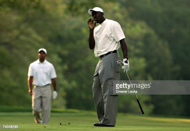 Tiger Woods watches basketball star Michael Jordan on the 4th fairway during the Proam at the Wachovia Championship at Quail Hollow Country Club on...