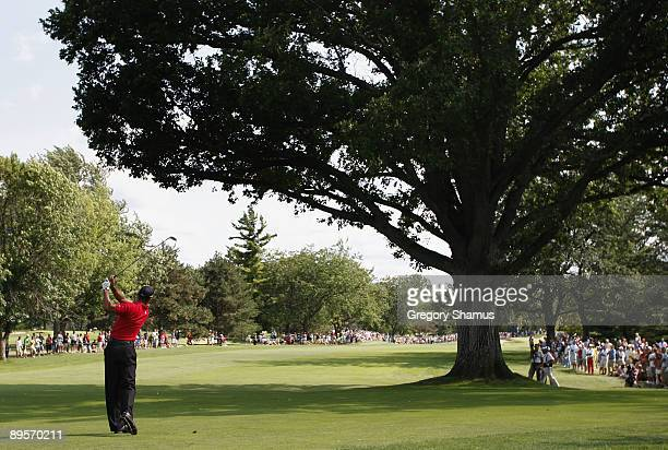 Tiger Woods watches his shot from behind a tree on the 13th hole during the final round of the Buick Open at Warwick Hills Golf and Country Club on...