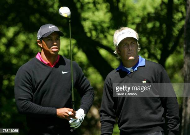 Tiger Woods watches his tee shot on the second hole as Stuart Appleby of Australia looks on during the final round of The Masters at the Augusta...