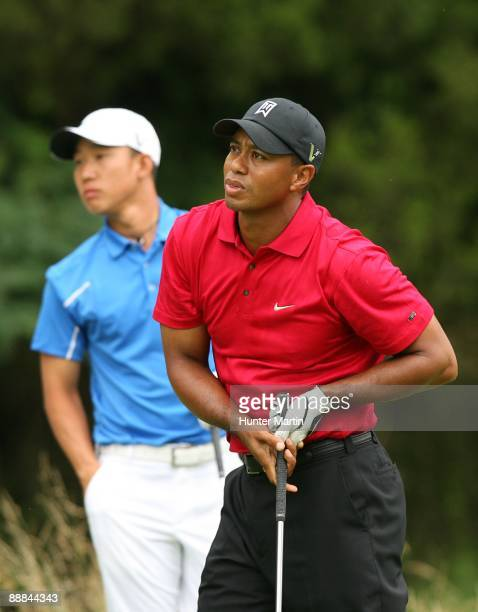 Tiger Woods watches his tee shot on the sixth hole as Anthony Kim looks on during the final round of the AT&T National hosted by Tiger Woods at...