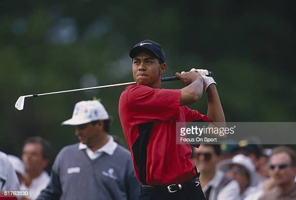 Tiger Woods watches the flight of his ball after teeing off during the Masters Tournament at the Augusta National Golf Club on April 13 1997 in...