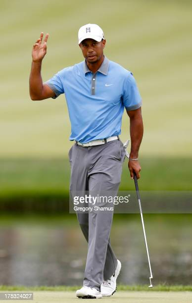 Tiger Woods waves after a birdie putt on the third green during the Second Round of the World Golf Championships-Bridgestone Invitational at...
