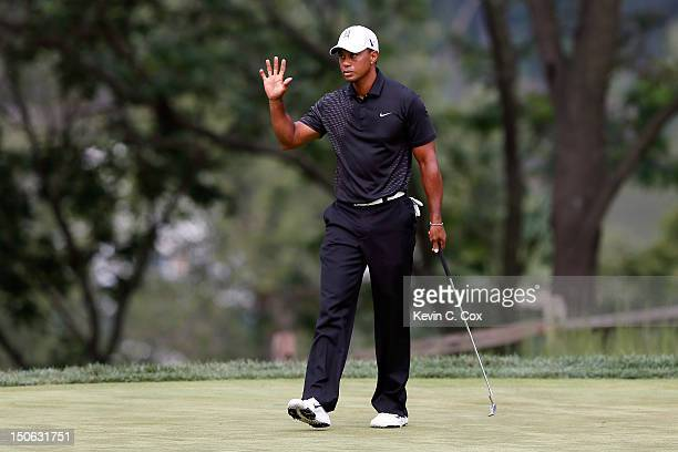 Tiger Woods waves after he made a birdie putt on the 14th hole during the First Round of The Barclays on the Black Course at Bethpage State Park...