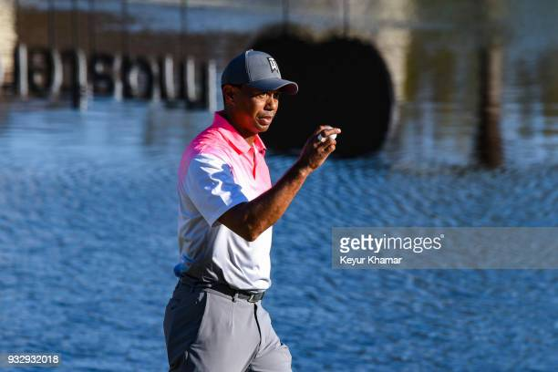 Tiger Woods waves his ball to fans after making a par putt on the 18th hole green during the second round of the Arnold Palmer Invitational presented...