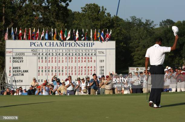 Tiger Woods waves his cap to the gallery on the 18th green after his 7-under par 63 during the second round of the 89th PGA Championship at the...