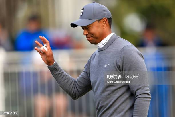 Tiger Woods waves to the crowd after a birde putt on the 17th green during the first round of the Valspar Championship at Innisbrook Resort...