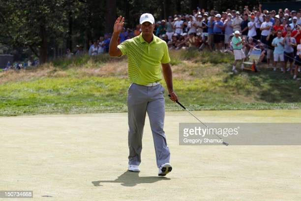Tiger Woods waves to the fans after he made a birdie putt fifth hole during the third round of The Barclays at the Black Course at Bethpage State...