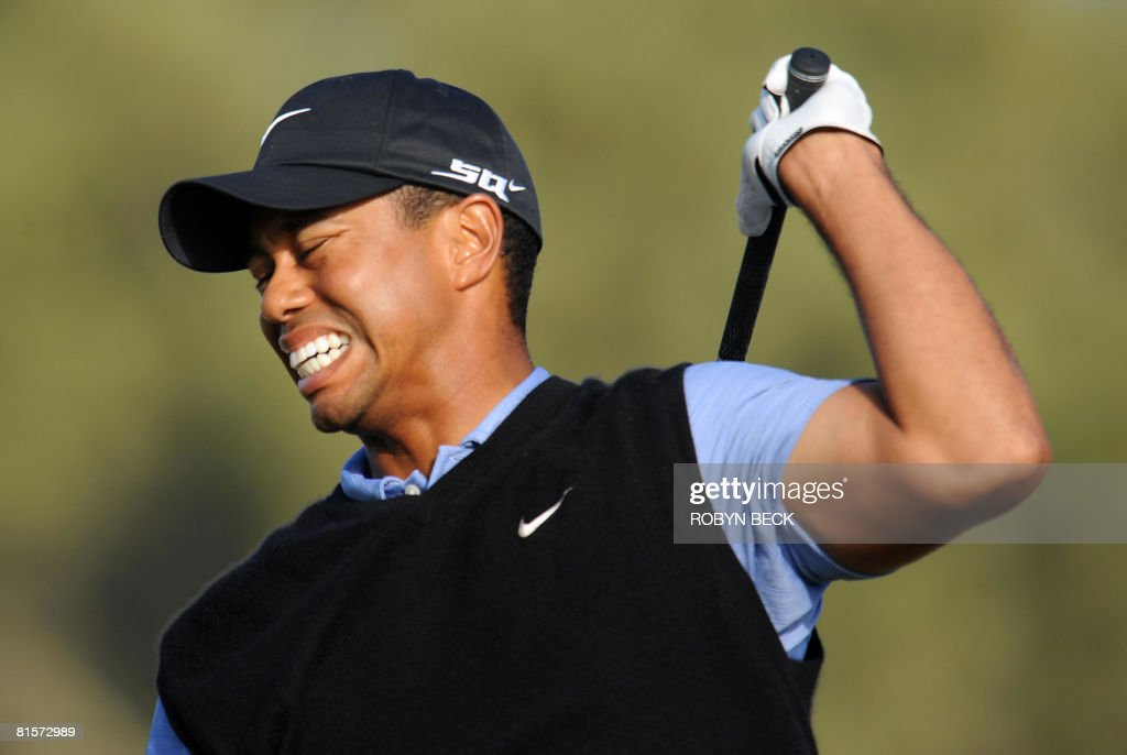 Tiger Woods winces in pain as he follows thru on his shot from the 15th tee, in the third round of the 108th U.S. Open golf tournament at Torrey Pines Golf Course in San Diego, California on June 14, 2008.