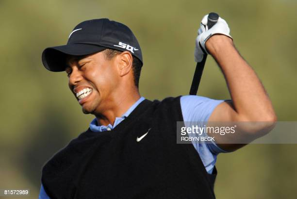 Tiger Woods winces in pain as he follows thru on his shot from the 15th tee in the third round of the 108th US Open golf tournament at Torrey Pines...