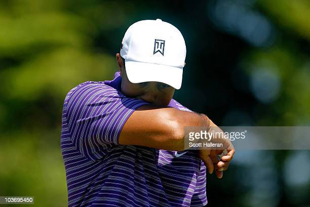 Tiger Woods wipes his face after a putt attempt on the green of the second hole during the third round of The Barclays at the Ridgewood Country Club...