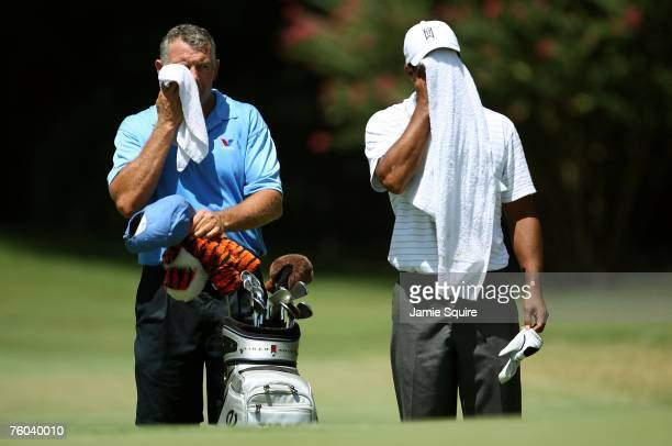 Tiger Woods wipes his face alongside his caddie Steve Williams during the first round of the 89th PGA Championship at the Southern Hills Country Club...