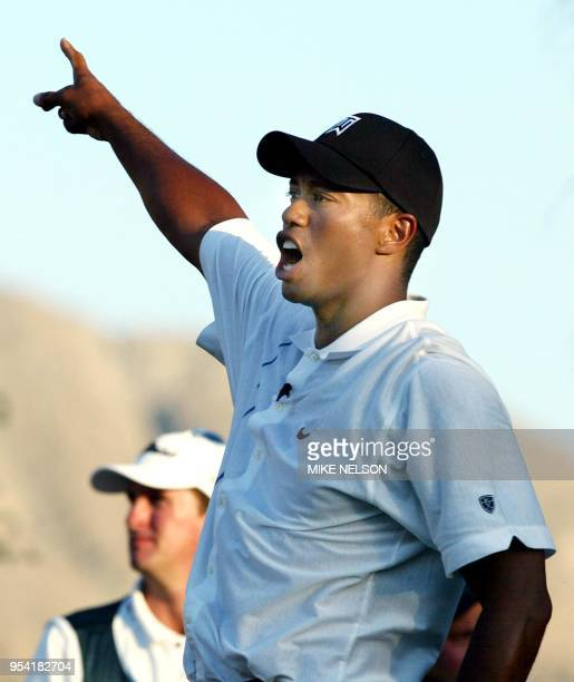 Tiger Woods yells and points to the right after hitting a tee shot on the 12th hole at the Battle at Bighorn 29 July 2002 at Palm Desert California...