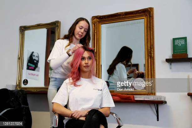Tigerlily has half her hair dyed by hairdresser Hannah Barrie as part of the Halfcut fundraising movement at Stanley and Co Barber Shop in...