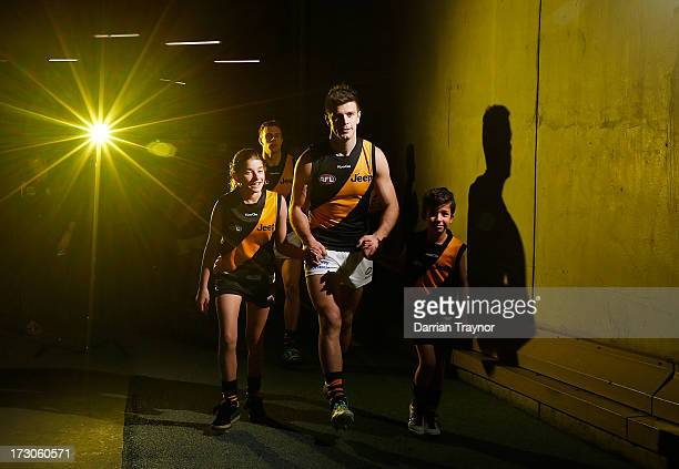 Tigers captain Trent Cotchin walks out with the team mascot before the round 15 AFL match between the North Melbourne Kangaroos and the Richmond...