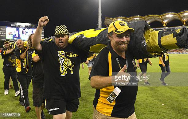 Tigers fans carry the banner before the round one AFL match between the Gold Coast Suns and the Richmond Tigers at Metricon Stadium on March 15 2014...