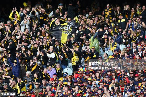 Tigers fans celebrates a goal next to silent Crows fans during the 2017 AFL Grand Final match between the Adelaide Crows and the Richmond Tigers at...