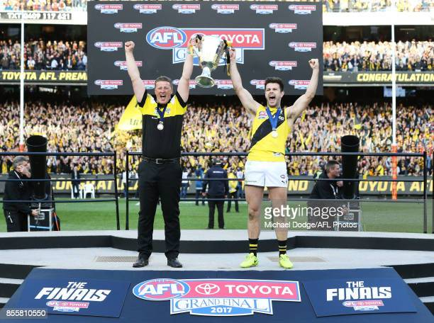 Tigers head coach Damien Hardwick and Trent Cotchin of the Tigers lift up the Premiership Cup after winning during the 2017 AFL Grand Final match...