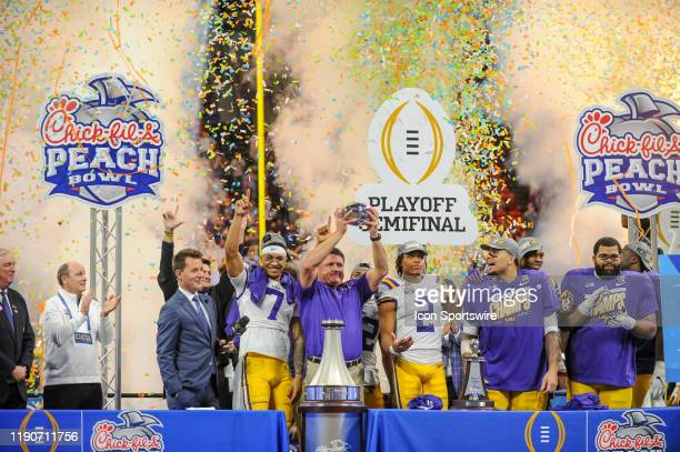 Tigers head coach Ed Orgeron raises the Peach Bowl trophy after winning the College Football Playoffs Semifinal ChickfilA Peach Bowl between the LSU...